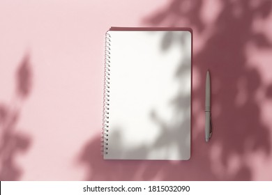 Open notebook mock up, pen  and floral shadows on pink background. copy space