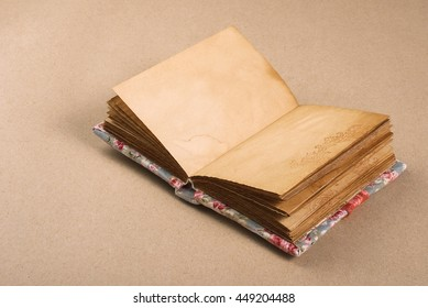 Open notebook old book lying on crafting background.
