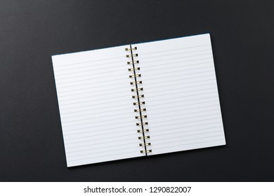 open notebook on black background top view, school notepad on a dark table, office desk flat lay