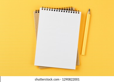 open notebook on corrugated yellow background with pencil top view, spiral notepad with blank sheet, flat lay. school concept, desktop of businessman.