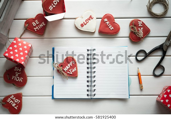 Open notebook on white wooden table with cookies in form of heart. St. Valentines Day concept. Eye bird view