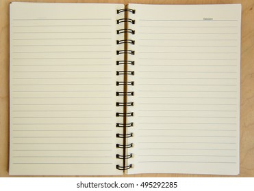 Open notebook on wooden background. ruled paper