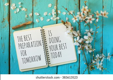 open notebook over wooden table with motivational saying the best preparation for tomorrow is doing your best today