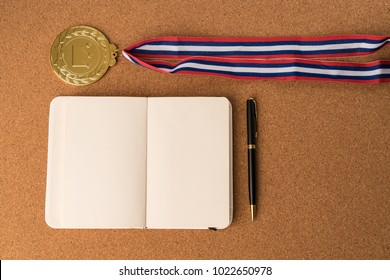open notebook paper with business ink pen with smart phone and Gold medal.flat lay style