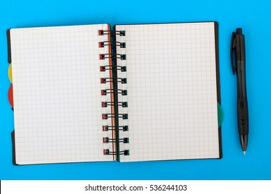 Open notebook with a pen on a blue background. Space for your text. Sports concept. Empty sheet of paper