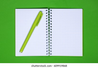 Open notebook and pen on a colored background