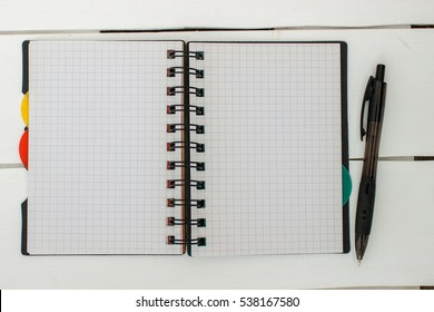 Open notebook with a pen on a White wooden boards. Space for your text. Sports concept. Empty sheet of paper