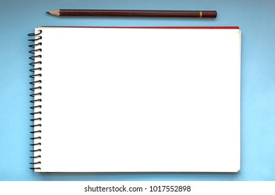 Open notebook with pencil on a blue background