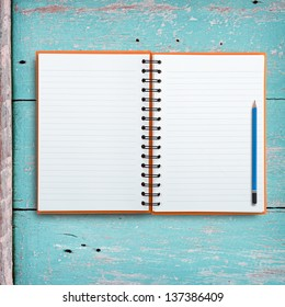 Open notebook with pencil on grunge wood background.