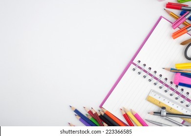 Open notebook and school or office tools on white background