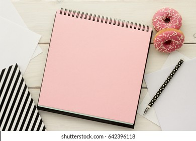 Open notebook, sketchbook or scrapbook with pink  blank page and snack - donuts on white wooden table.  Ideas, notes,  plan writing or sketching concept. Top view.