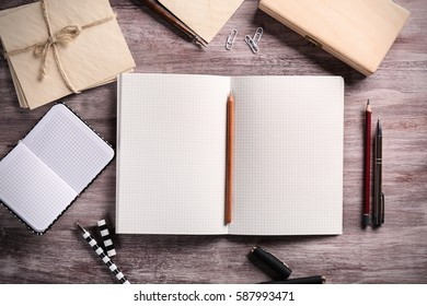 Open notebook with stationery on wooden background