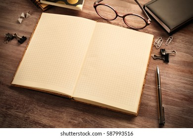 Open notebook with stationery on wooden table