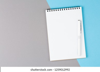 open notebook with white pen on blue  and gray table top view, notepad with blank page. flat lay of office concept