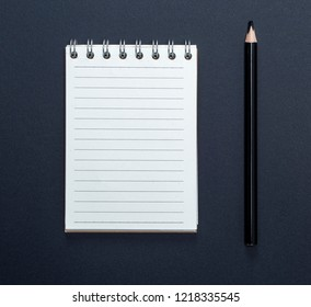 open notebook with white sheets in line and black wooden pencil on black background