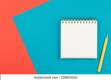 open notebook with a yellow pencil on two-color background blue and coral pink, top view, spiral notepad with blank sheet on the table flat lay