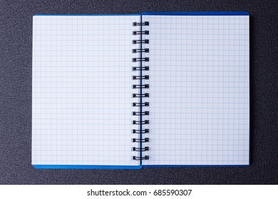 Open notepad on a spiral on a black background