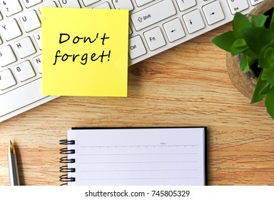 "Open notepad and sticky notes with word ""don't forget"" on top of wooden table"