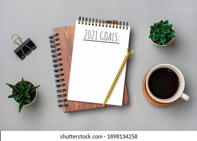open notepad with text 2021 goals, cup of coffee, succulents, golden pen on gray background, spiral notebook on table Business, planning, education concept Top view Flat lay