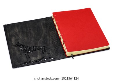 An open notepad with a wooden cover in which a carved animal.