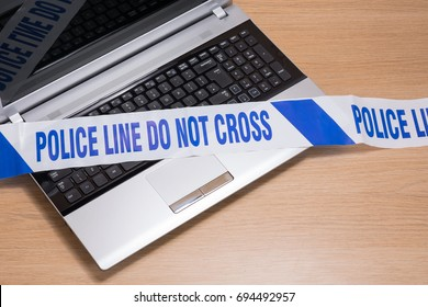 An open office computer laptop on a plain timber desk with police crime scene tape across the keyboard.