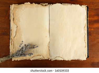 Open old book and lavander  on wooden background