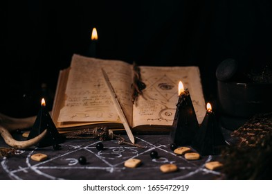 Open old book with magic spells, runes, black candles on witch table. Occult, esoteric, divination, superntural and wicca concept. Halloween vintage background