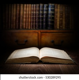 Open old book on a bookshelf background. Selective focus