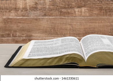 An open old book on a wooden table on a background of boards