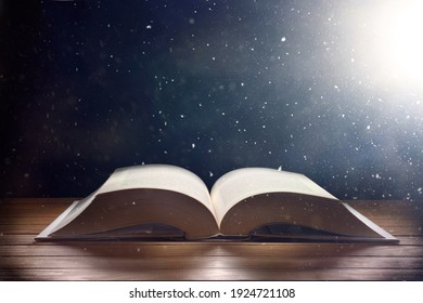 Open old book on wooden table and dark background with light shine and flying particles with mystical and imaginative look