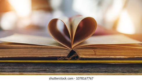 an open old book with sheets in the shape of a heart
