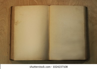 An open old book with yellowed pages on a wooden table