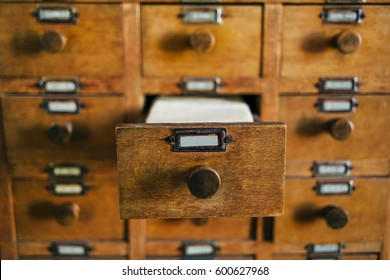 Open old style wooden drawer with index cards. Archive database concept