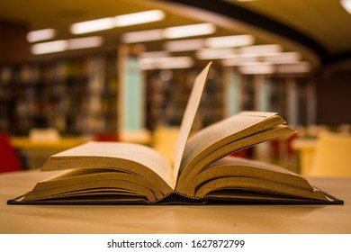 Open old textbook with the blurred background of bookshelves in radius plan inside the school library. For academic education learning concept.