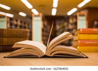 Open old textbook in front of two piles of blur literature texts in the college library with blur background of aisles of bookshelves in radius plan. For academic education learning concept.