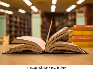 Open old textbook with a pile of literature texts in the college library. For academic education learning concept. Copy space.