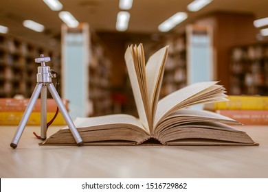 Open old textbook with small tripod nearby on working table in academic library (school, college, university, institute, or campus). With the blurred background of aisles of bookshelves. For academic