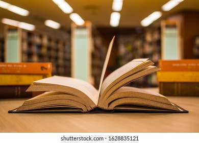 Open old textbook with two piles of literature texts in the school library. For traditional education learning concept.