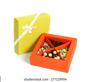 Open orange box full with candy and closed yellow box with ribbon on white background.