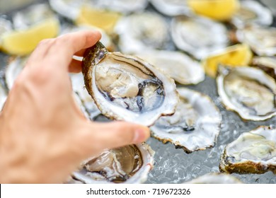 Open oyster in a man's hand, against a background of open oysters, close-up.