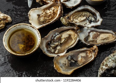 Open oysters on ice and knife on dark concrete texture background