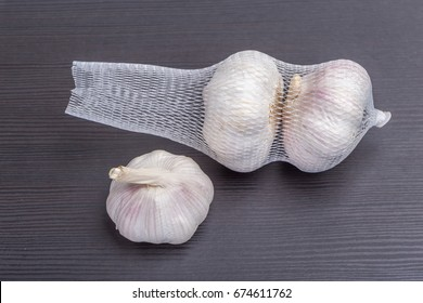 Open packaged white garlic bulbs in net place on wooden table, general and useful seasoning for tasty foods.
