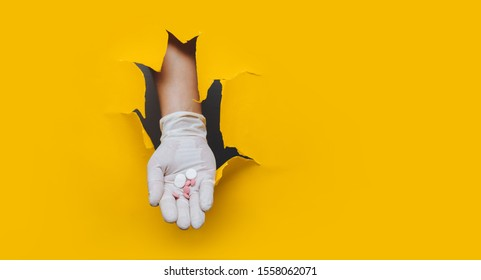 The open palm of white rubber glove with white and pink pills. Medical theme Isolated on the yellow background. The concept of drug treatment, placebo and homeopathy. Torn paper hole, copy space.