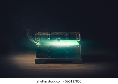 open pandora's box with green smoke on a wooden background /high contrast image