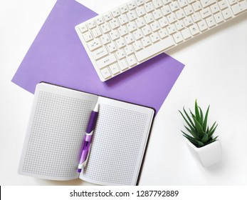 Open paper notebook, white computer keyboard, purple pen and decorative green plant. Flat lay office table