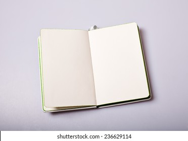 Open paper notepad with blank pages on white table