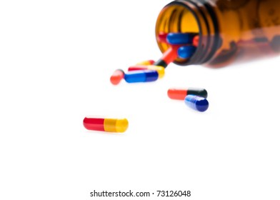Open pharmaceutical bottle which spills colored capsules over white