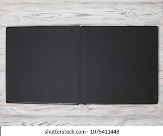 open photobook on a wooden background. black photo album on white background