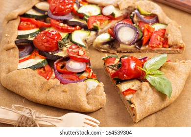 Open pie with vegetables on baking paper
