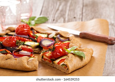Open pie with vegetables on a wooden table